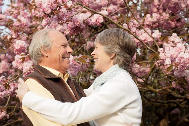 Marido y mujer abrazando en jardín - foto de stock