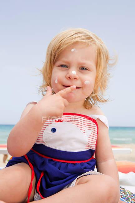 Menina bebê com creme solar no rosto — Fotografia de Stock