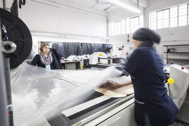 Trabalhadores femininos da fábrica que desenrolam têxteis na máquina de corte padrão na fábrica de roupas — Fotografia de Stock