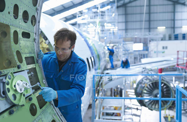 Engineer working on aircraft door in aircraft maintenance factory — Stock Photo