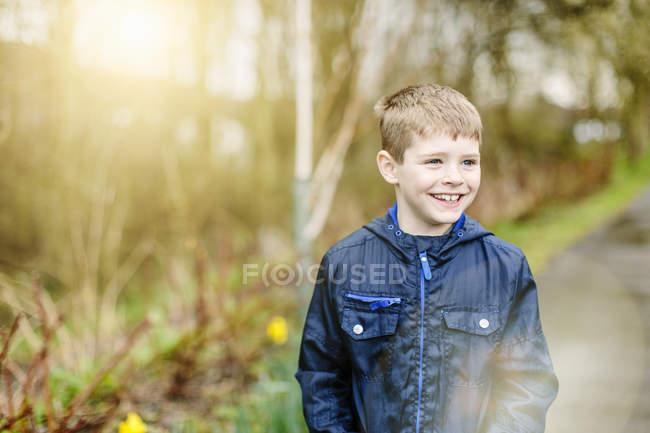 Menino de pé ao ar livre na floresta em luz suave — Fotografia de Stock