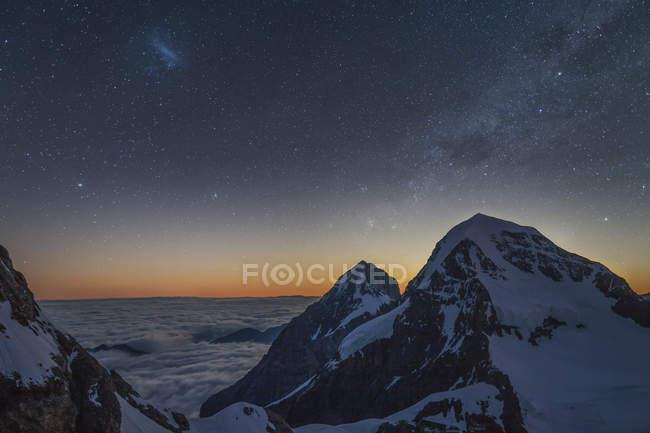 Cumbres nevadas y cielo estrellado iluminado - foto de stock