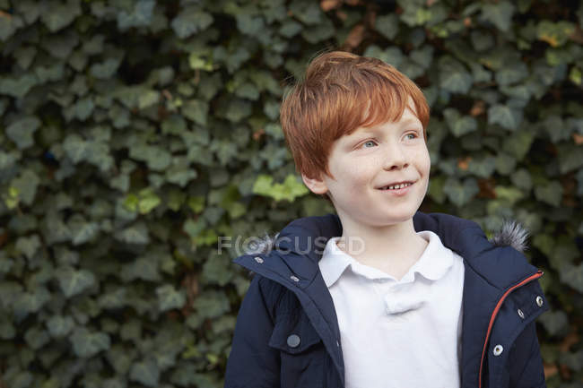 Portrait of red haired boy in front of ivy wall looking away — Stock Photo