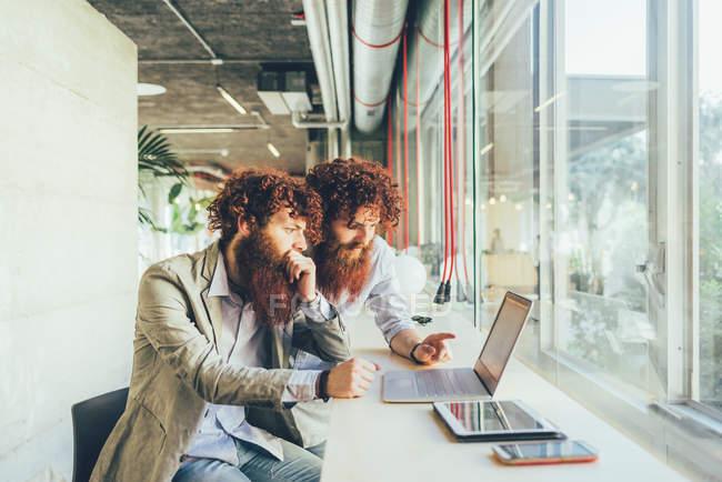 Gemelli hipster adulti maschi che puntano al computer portatile in ufficio — Foto stock