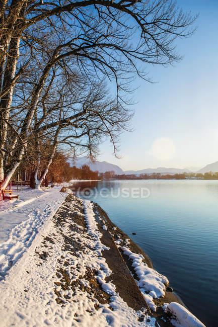 Verschneite Bank und noch ländliche See bei Sonnenuntergang — Stockfoto