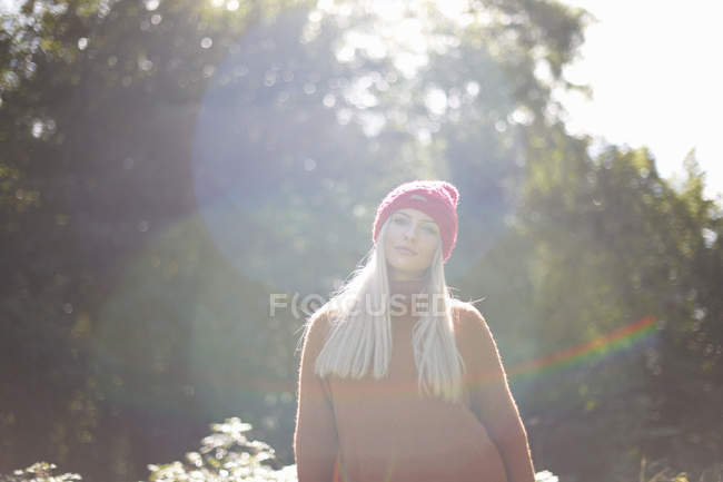 Portrait of woman in forest wearing knit hat looking at camera — Stock Photo