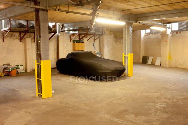 Auto in copertina nera parcheggiata nel garage — Foto stock