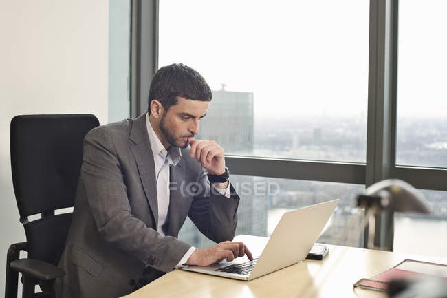 Businessman working on laptop in office interior — Stock Photo