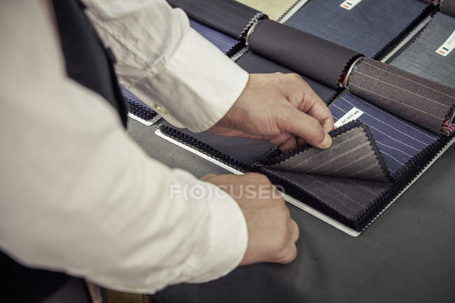 Портной выбирает ткань из образцов в магазине портных — стоковое фото