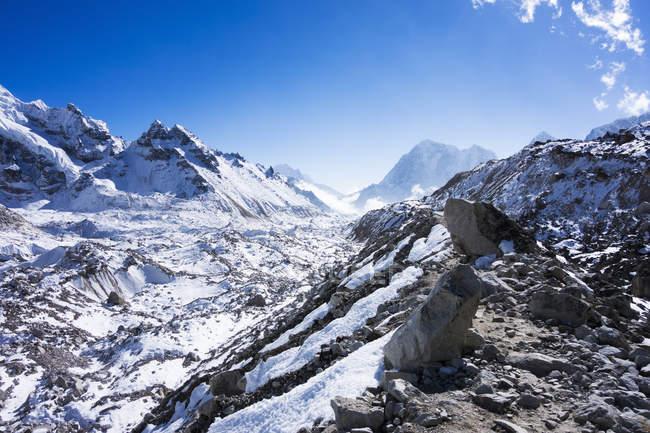 Vista panoramica delle montagne innevate con cielo blu — Foto stock