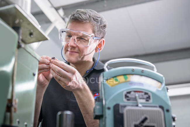 Engineer in safety glasses polishing steel parts for industry — Stock Photo