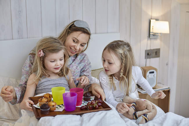 Mother and daughters having breakfast in bed — Stock Photo