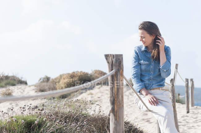 Mitte Erwachsene Frau sitzen auf Seil eingezäunt Sanddüne, Sardinien, Italien — Stockfoto