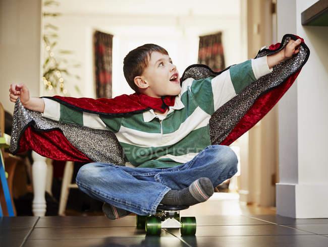 Молодий хлопчик, сидячи на скейтборді носіння мис — стокове фото
