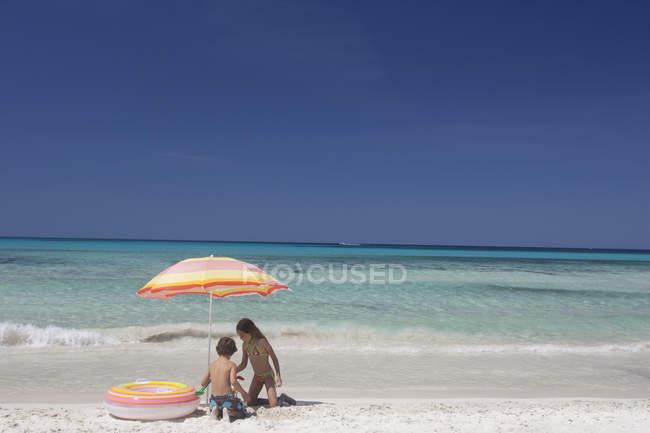 Девочка и брат играют под пляжным зонтиком на пляже, Майорка, Испания — стоковое фото