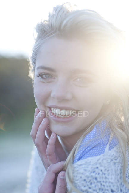 Portrait of young woman huddled up in blanket — Stock Photo