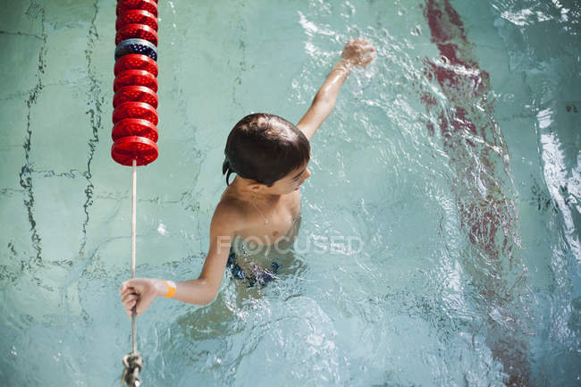 High angle view of boy holding onto rope in swimming pool — Stock Photo