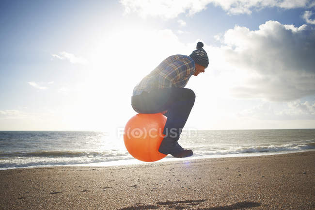 Mature man jumping mid air on inflatable hopper at beach — Stock Photo