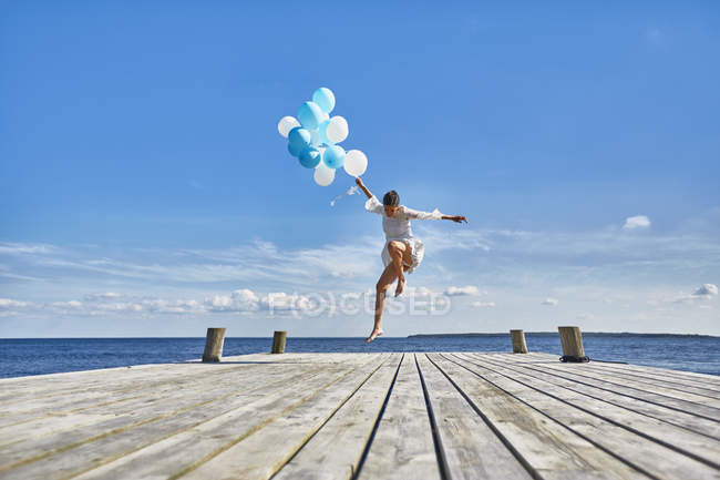 Giovane donna che balla sul molo di legno, tenendo mazzo di palloncini — Foto stock