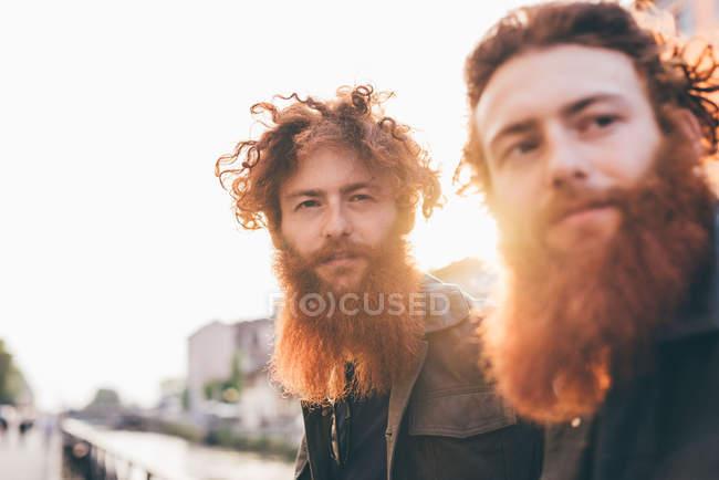 Jovens gêmeos hipster masculinos com cabelos vermelhos e barbas na orla do canal — Fotografia de Stock