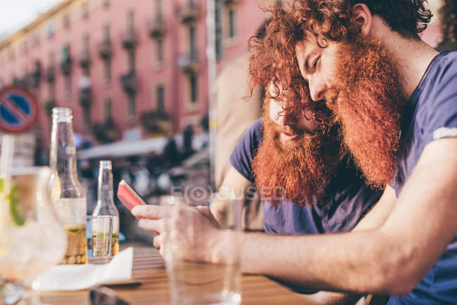 Young male hipster twins with red hair and beards reading smartphone texts at sidewalk bar — Stock Photo
