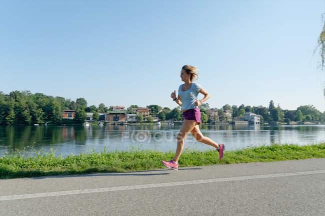 Взрослая женщина бежит по дороге вдоль озера — стоковое фото