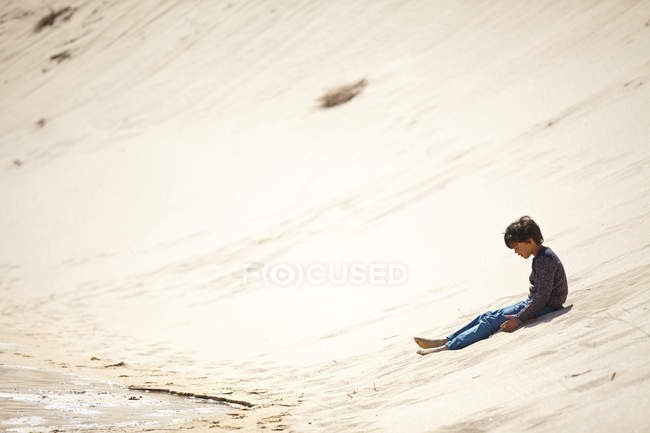 Young boy sitting on sandy hill — Stock Photo
