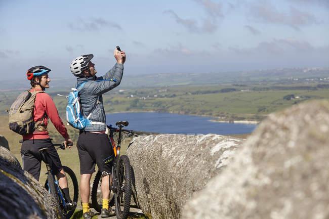 Ciclisti con le biciclette su foto di cattura di affioramento roccioso — Foto stock