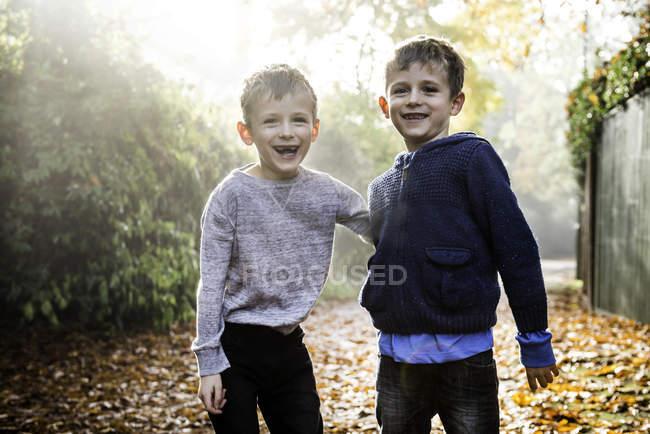 Портрет близнецов, на открытом воздухе, в окружении осенних листьев, смеющиеся — стоковое фото