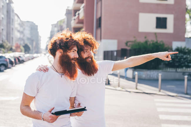 Young male hipster twins with red hair and beards pointing on city street — Stock Photo