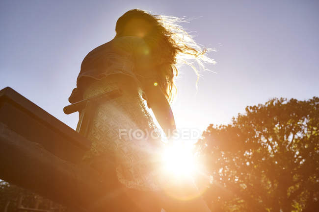 Girl sitting on see-saw, bright sunlight shining through trees, low angle view — Stock Photo