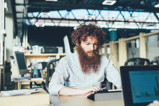 Молодой хипстер, использующий цифровой планшет за столом — стоковое фото