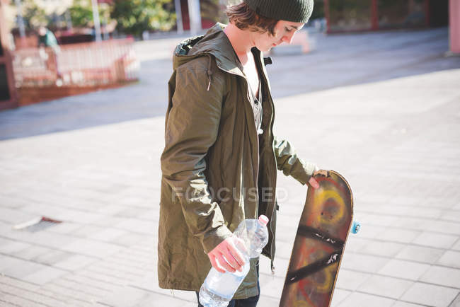 Young male urban skateboarder holding bottle of water — Stock Photo