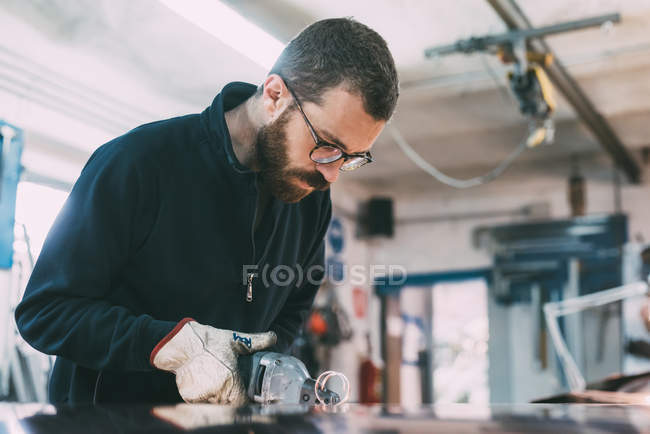 Metalworker cutting copper sheet with electric hand shears at forge workbench — Stock Photo