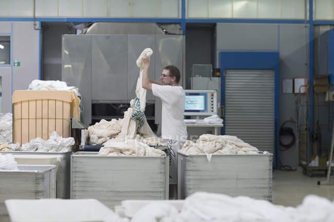Человек, работающий в прачечной launderette — стоковое фото