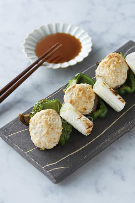 Nourriture japonaise servie sur ardoise avec baguettes et sauce à tremper — Photo de stock