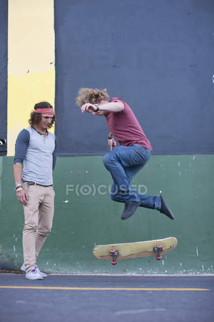 Young adult male doing skateboarding trick on city street — Stock Photo