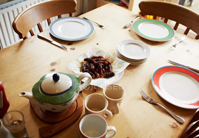 Teekanne, Tassen und Teller setzen auf Holztisch — Stockfoto