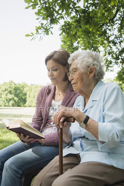 Femme aîné et petite-fille mûre s'asseyant sur la bible de lecture de banc de stationnement — Photo de stock