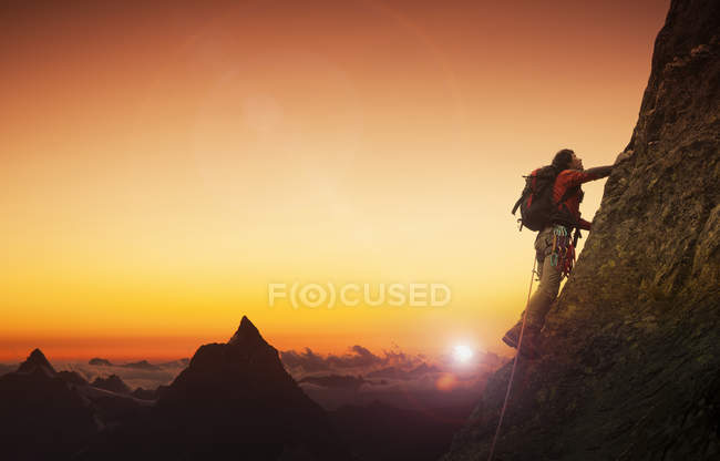 Escalador em uma parede rochosa com o Matterhorn ao pôr do sol, Zermatt, Cantão Wallis, Suíça — Fotografia de Stock