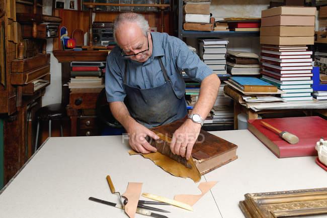 Старший чоловік ремонту антикварні книга хребта в традиційних палітурне майстерні — стокове фото