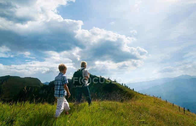 Отец и сын путешествуют по травянистой вершине холма — стоковое фото