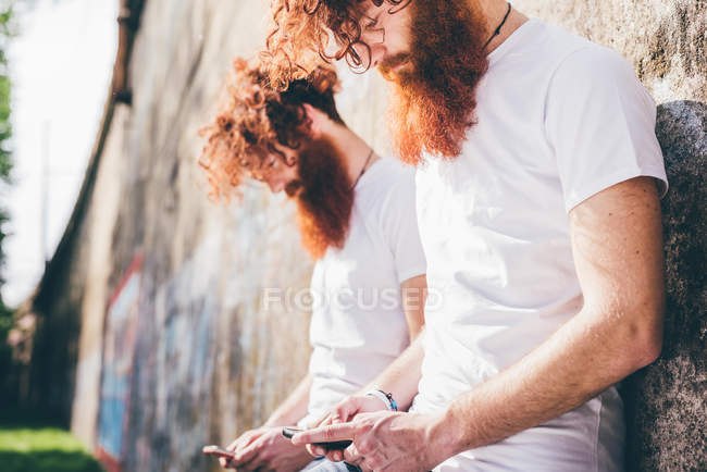 Young male hipster twins with red beards leaning against wall texting on smartphones — Stock Photo