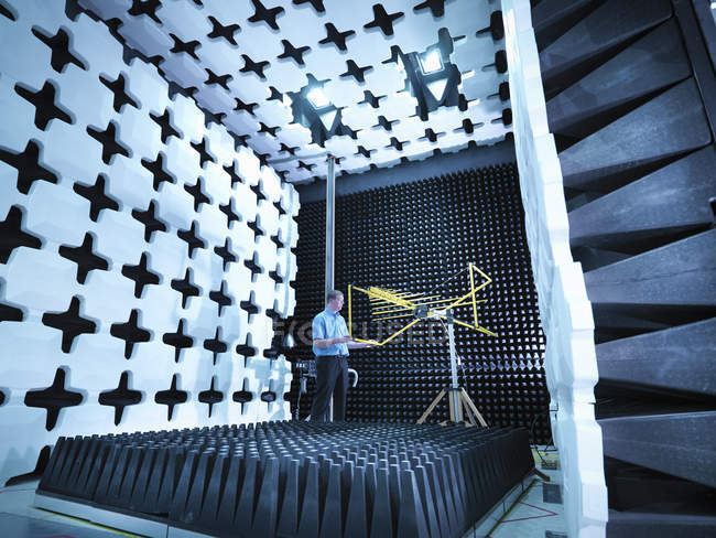 Engineer checking the bilog antenna set up for electromagnetic compatibility (EMC) radiated emissions in anechoic chamber with energy absorbers — Stock Photo