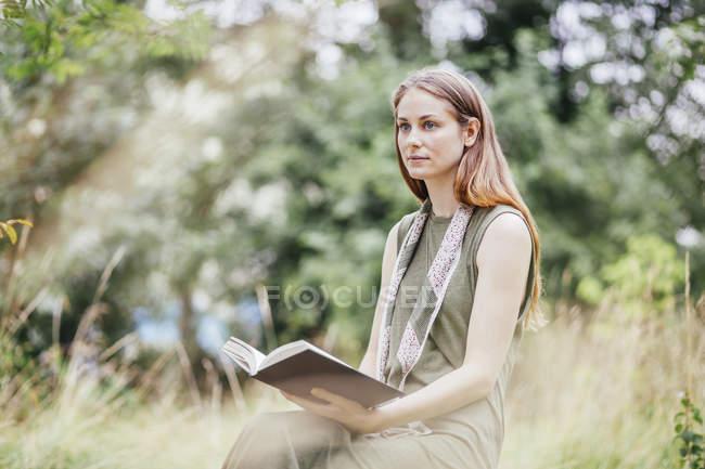 Mujer joven en el campo distraída de leer libro - foto de stock