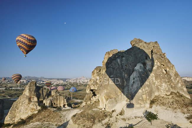 Sombra de globos de aire caliente en roca formación, Capadocia, Anatolia, Turquía - foto de stock