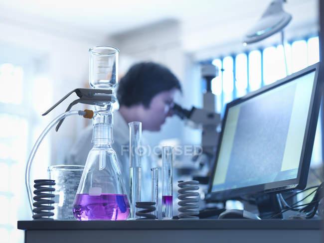 Métallurgiste en arrière-plan travaillant en laboratoire avec des produits chimiques sur bureau par ordinateur — Photo de stock