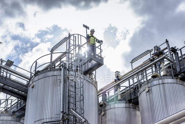 Travailleur sur le dessus de l'usine de traitement dans l'usine de mélange d'huile — Photo de stock