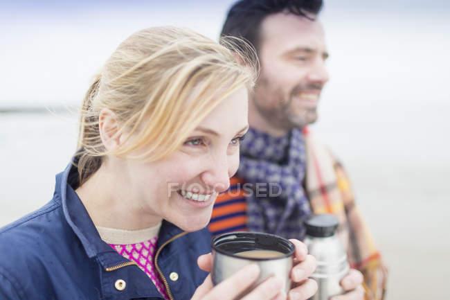 Paar am Strand trinkt Heißgetränk aus Flasche und Thermoskanne — Stockfoto