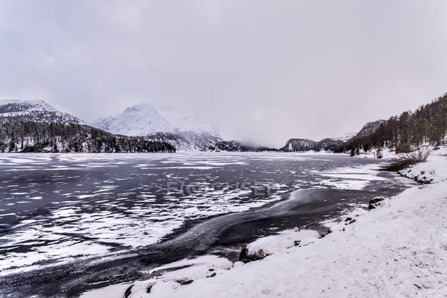 Lago congelado e montanhas coberta de neve sob céu nublado — Fotografia de Stock